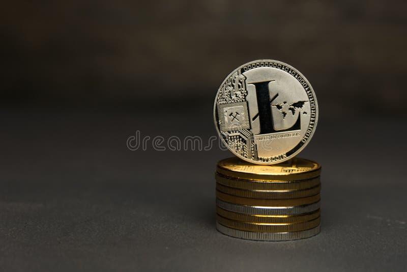 Серебряная стойка litecoin на куче монеток на темной предпосылке стоковые фото