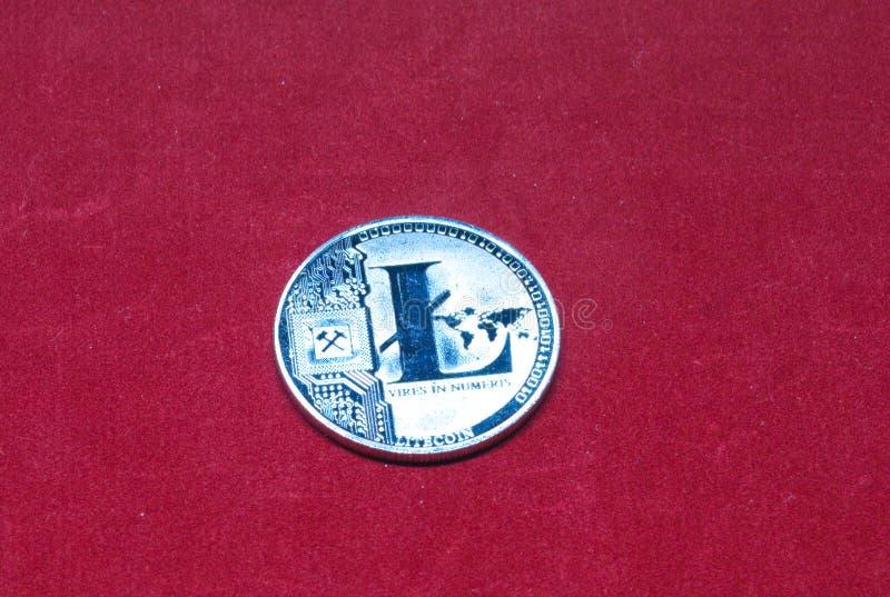 Серебряное litecoin на красной предпосылке стоковое фото