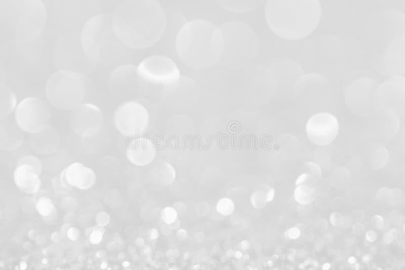 Серебряные белые блестящие света рождества Запачканная абстрактная предпосылка стоковая фотография