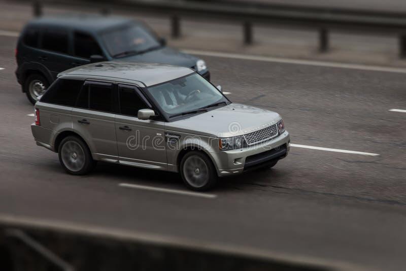 Серебряные езды Range Rover на дороге Против предпосылки запачканных деревьев стоковое фото rf