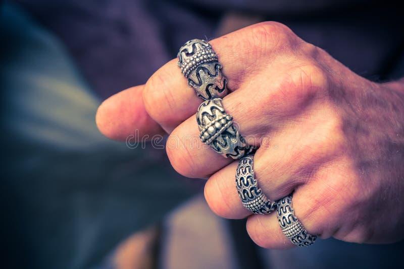 Серебряные знаки с средневековым скандинавским дизайном на пальцах плотной руки стоковое изображение