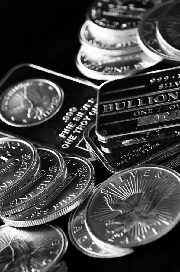 Серебряные монеты и бары представляя богатство стоковое фото