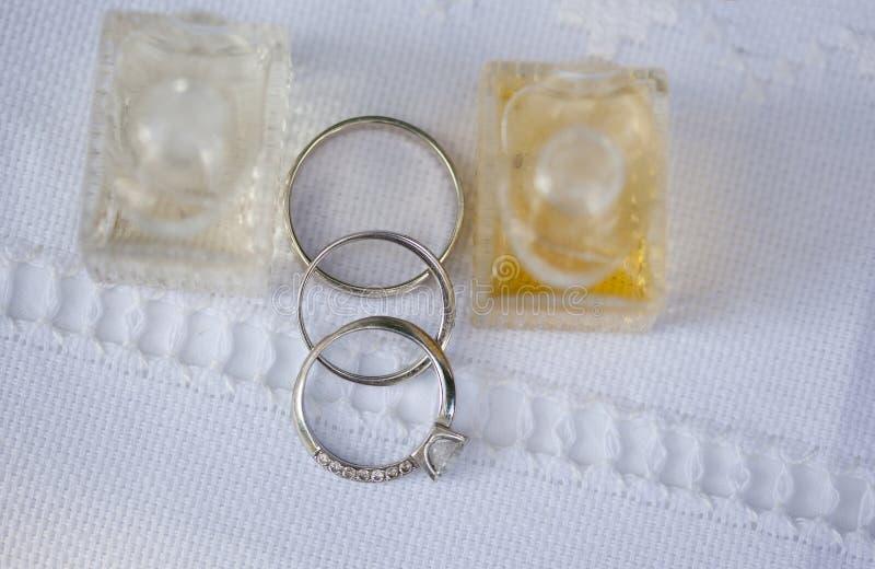 Серебряные обручальные кольца и обручальное кольцо и 2 бутылки parfume стоковые изображения