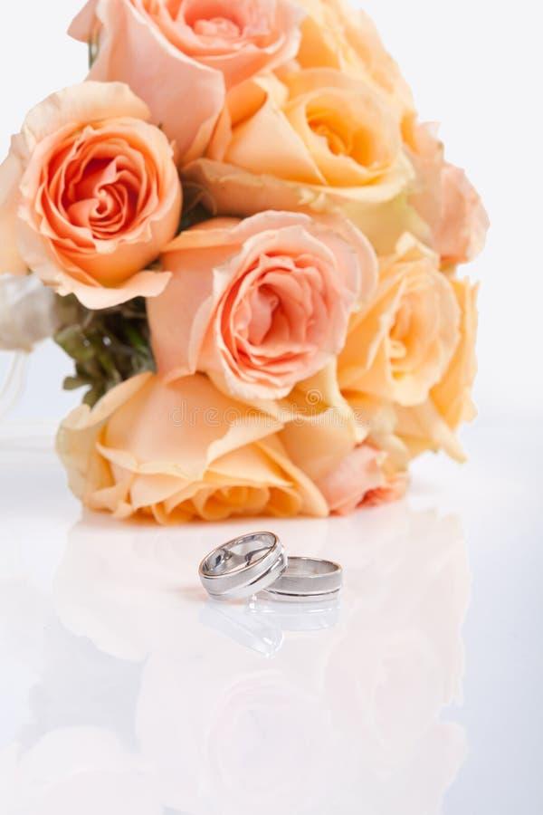Серебряные обручальные кольца и bridal букет стоковое изображение