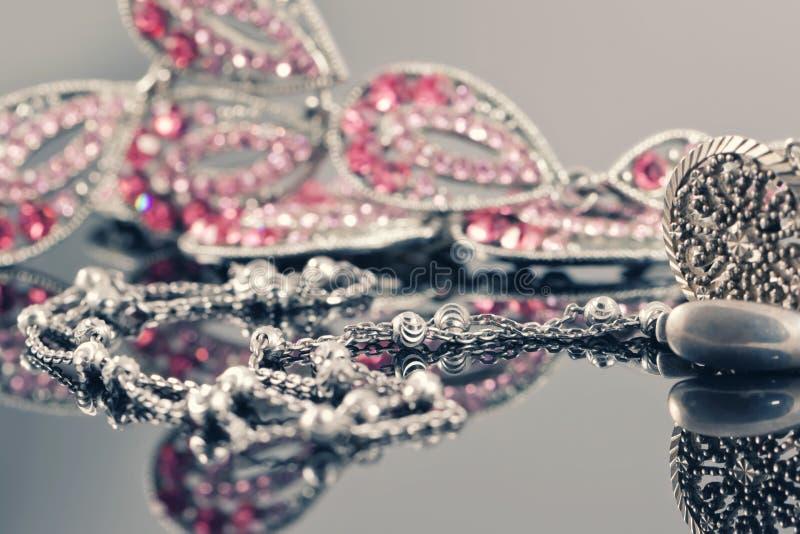 Серебряные ювелирные изделия на предпосылке украшений с розовыми камнями стоковое изображение