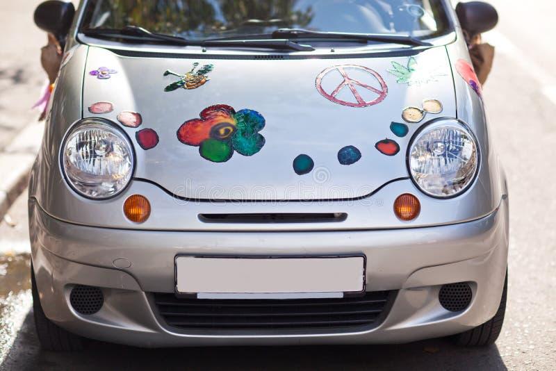 Серебряный автомобиль с покрашенными цветками на клобуке стоковое изображение