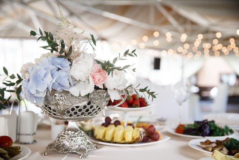 Серебряный бак с букетом цветка в нем стоит на таблице наряду с некоторыми плитами с едой стоковое фото