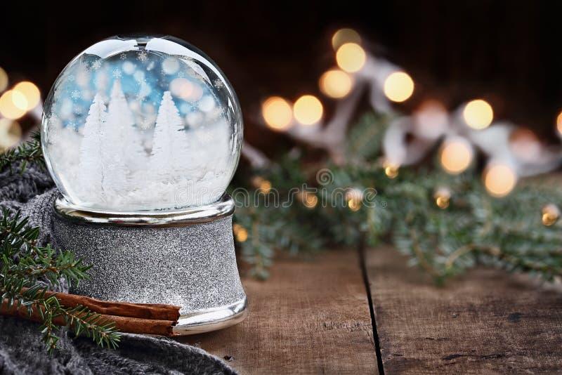 Серебряный глобус снега с миниатюрными белыми рождественскими елками стоковые фотографии rf