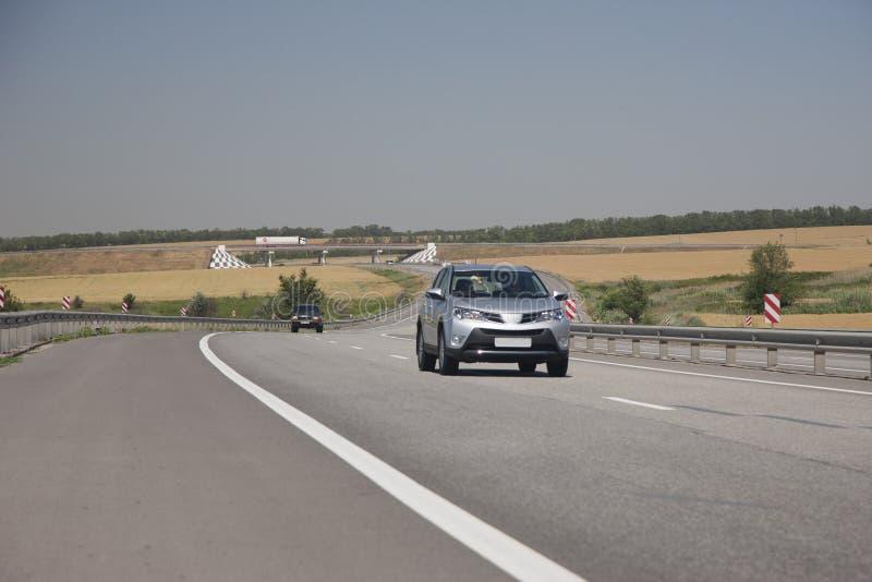 Серебряный кроссовер едет шоссе В расстоянии видит замотке дороги дороги стоковое изображение rf