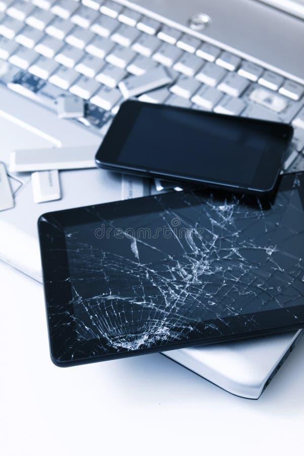 Серебряный ноутбук со сломленной клавиатурой, планшетом с треснутым дисплеем и черным телефоном Изображение конца-вверх части сло стоковая фотография