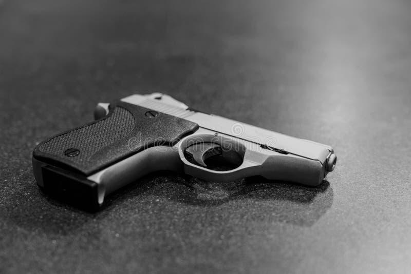 Серебряный пистолет изолированный на темной черноте таблицы & белый стоковые изображения rf