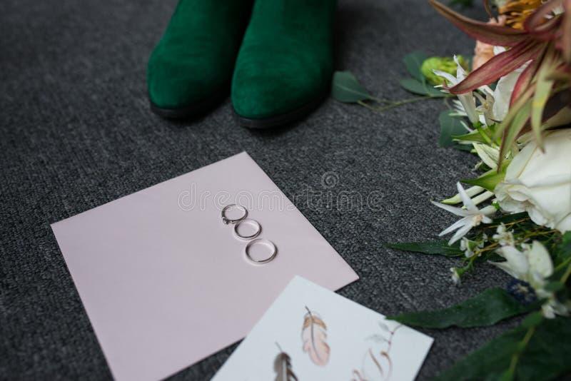 2 серебряных обручального кольца и обручальное кольцо на конверте Зеленые bridal ботинки, часть букета свадьбы и compl свадьбы стоковые фотографии rf
