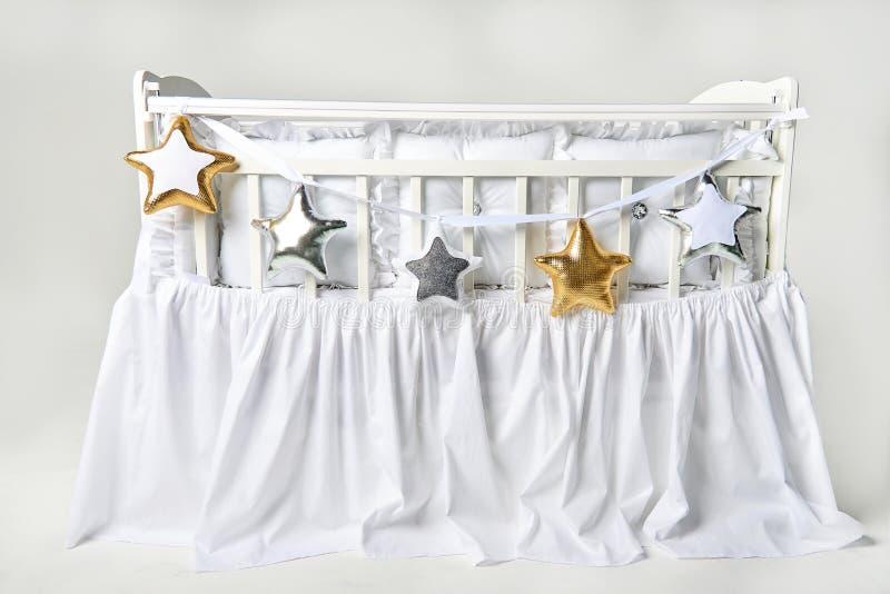 Серебр, золото и белая звезда сформировали подушки на белой кроватке младенца стоковая фотография rf