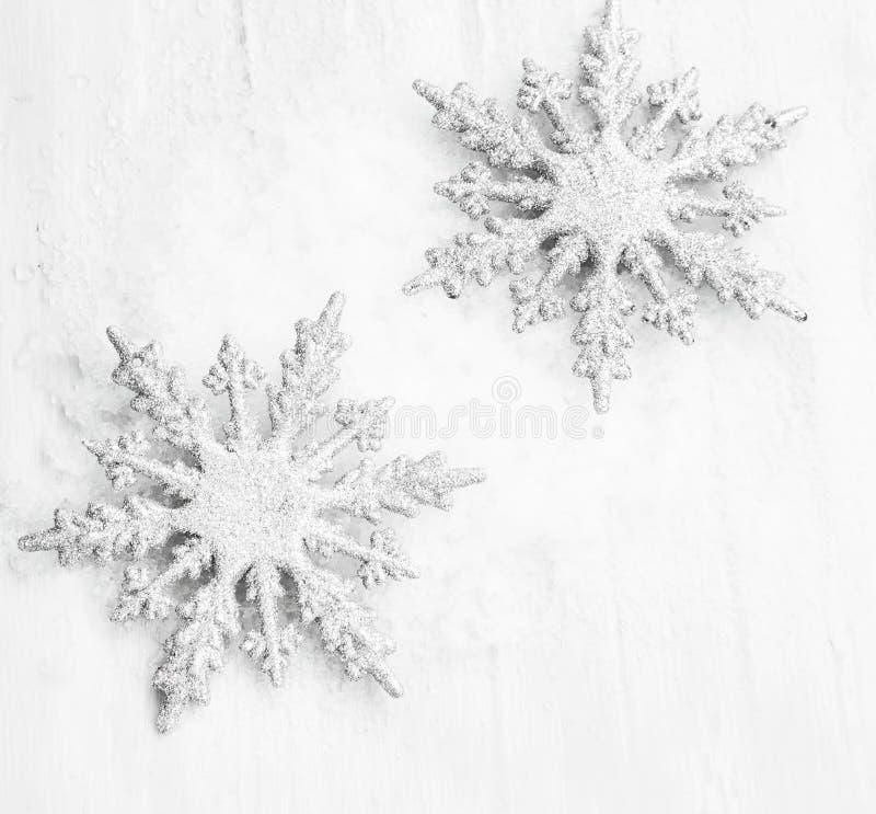 Серебр 2 Glittered орнаменты снежинок в снеге стоковые изображения