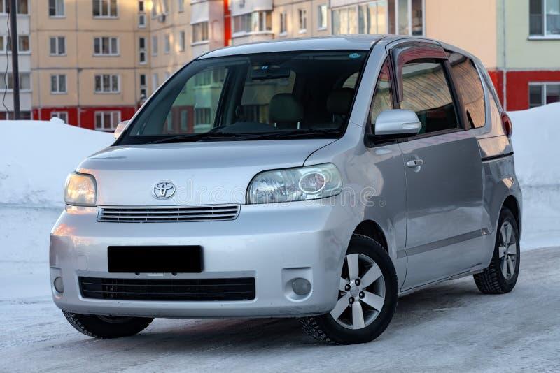 Серебр porte Тойота бренда семейного автомобиля в улице в зиме, минифургоне подготовленном для продажи против фона города стоковые изображения rf