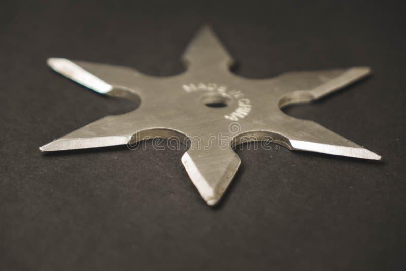 Серебр shuriken на черной предпосылке, бросая оружия стоковая фотография