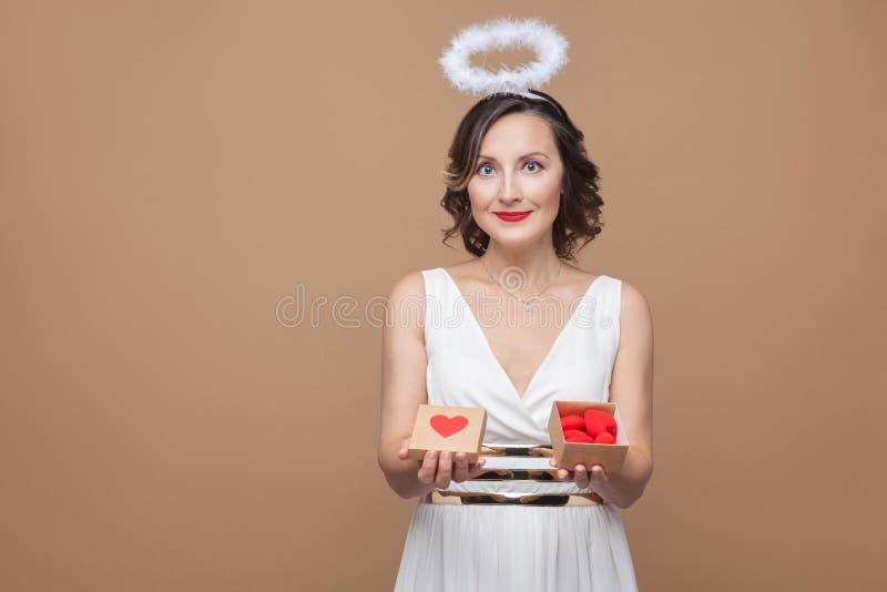 Середина постарела женщина ангела в белом платье и nimbus держа подарок b стоковые фотографии rf