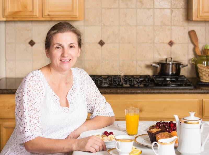 Середина постарела женщина имея завтрак в кухне стоковая фотография rf