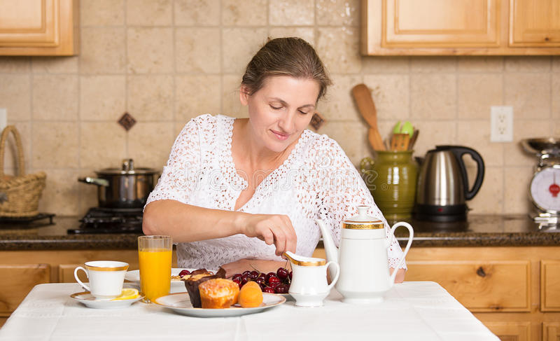 Середина постарела женщина имея завтрак в кухне стоковое фото rf