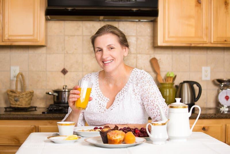 Середина постарела женщина имея завтрак в кухне стоковые фото