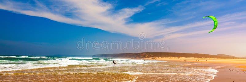 Серферы в пляже da Bordeira Прая около Carrapateira, Португалии Спортсмен kitesurfer Kiteboarder выполняя kitesurfing kiteboardin стоковые изображения
