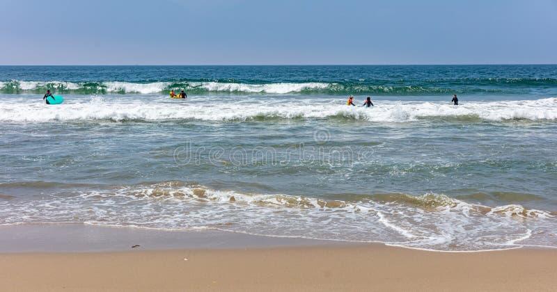 Серферы идя заниматься серфингом, волны моря океана в солнечном весеннем дне стоковое изображение