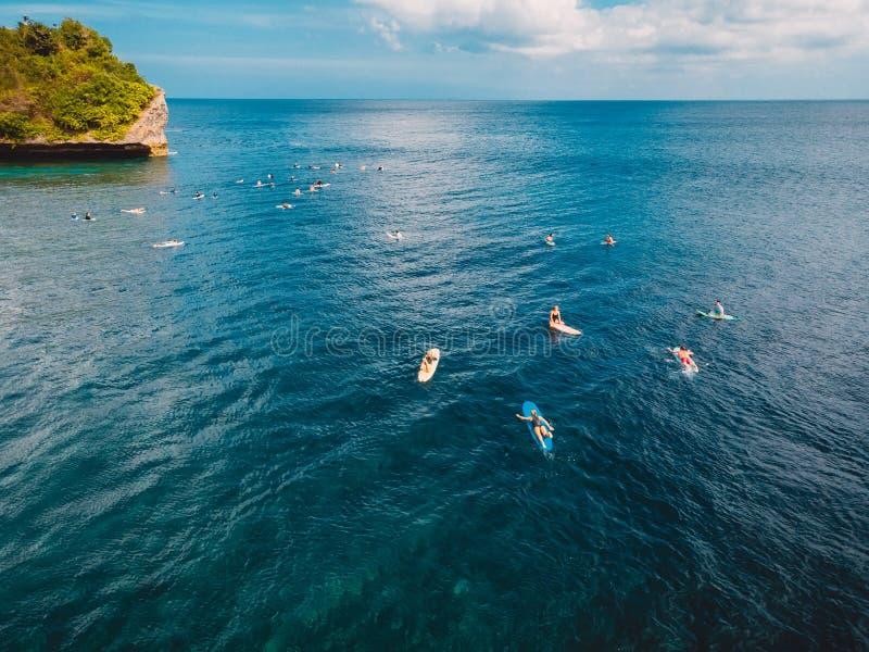Серферы с surfboards в волне океана ждать стоковые изображения rf