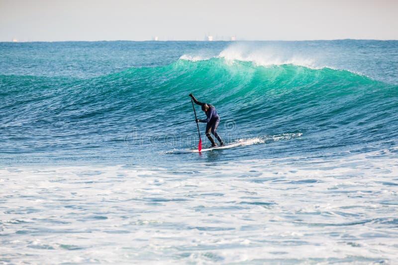 Серфер дальше стоит вверх доска затвора на голубой волне Зима занимаясь серфингом в океане стоковые изображения
