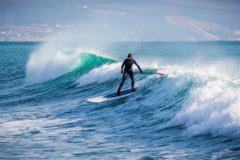 Серфер дальше стоит вверх езда доски затвора на волне Зима занимаясь серфингом в океане стоковая фотография rf