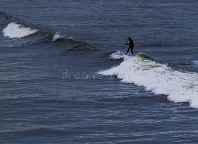 Серфер держа весло в волнах мокрой одежды обсуждая на Tynemouth стоковые изображения rf