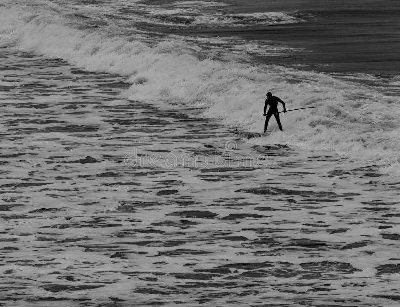 Серфер держа весло в волнах мокрой одежды обсуждая на Tynemouth стоковое фото