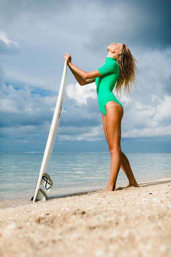 Серфер женщины с доской в руках на пляже стоковое фото rf