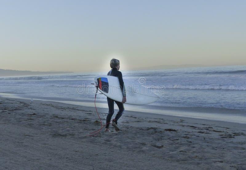 Серфер мальчика идя в океан стоковые фотографии rf