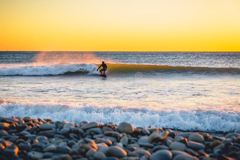 Серфер на заходе солнца или восходе солнца Серфинг зимы холодный в мокрой одежде стоковое изображение rf