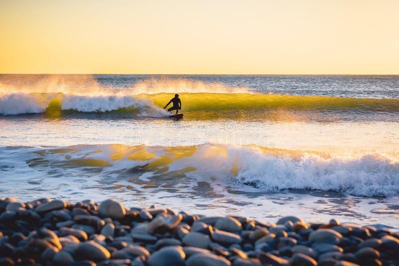 Серфер на океанской волне на заходе солнца или восходе солнца Зима занимаясь серфингом в мокрой одежде стоковые изображения