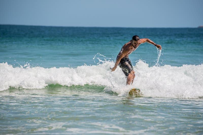 Серфер на Ilha большом, пляже Mendes прыжков смешно Бразилия Рио делает стоковое изображение rf