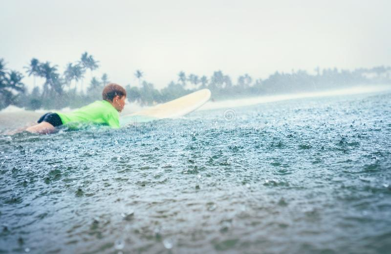 Серфер первого шага мальчика уча заниматься серфингом под тропическим дождем стоковое изображение