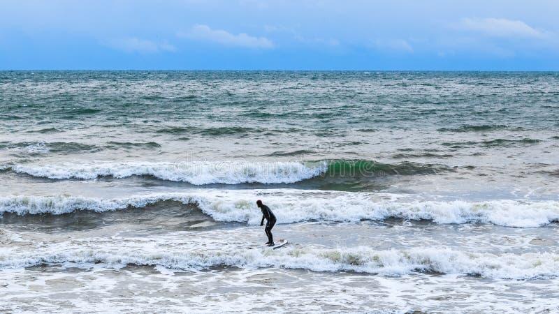 Серфер пробует ехать на интенсивных волнах стоковое фото rf