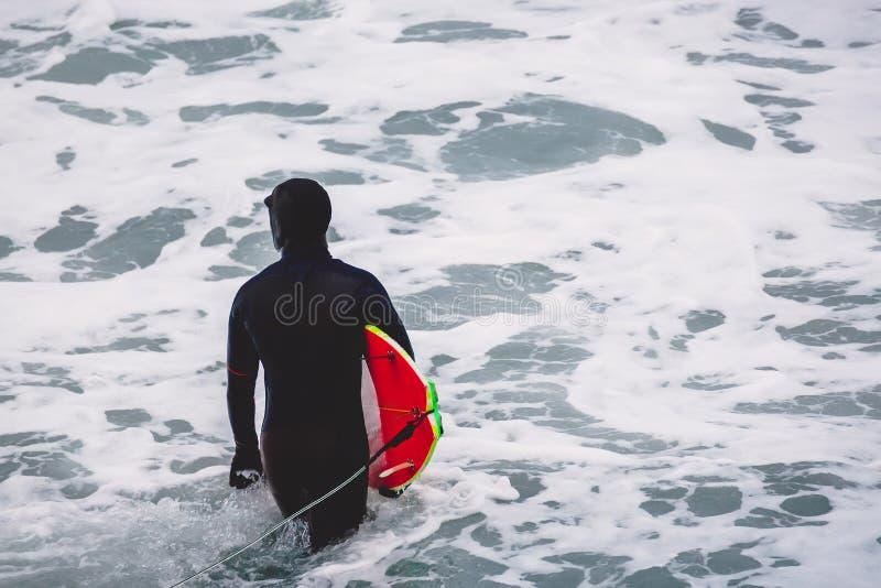 Серфер с surfboard в океане Серфер в мокрой одежде стоковая фотография rf