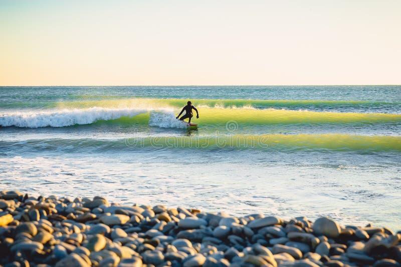 Серфинг на океанской волне на заходе солнца или восходе солнца Зима занимаясь серфингом в мокрой одежде стоковые фотографии rf