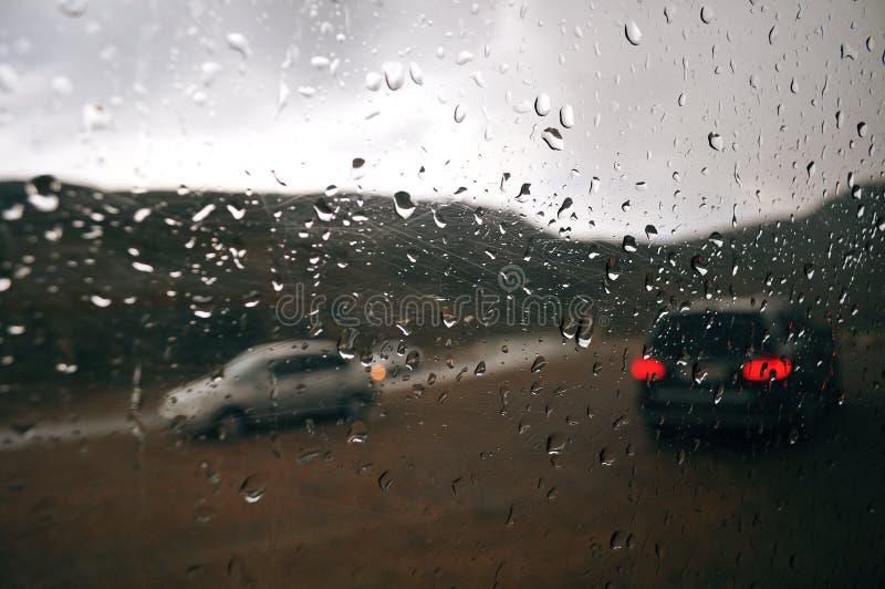 Серые дождевые капли на окне автомобиля на пасмурный день Вне окна силуэтов автомобиля проходить автомобили стоковая фотография rf