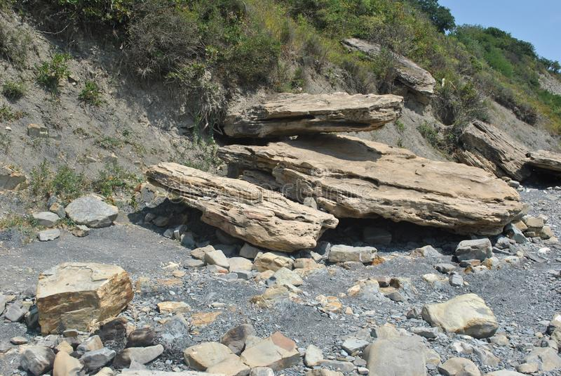 Серые и бежевые камни на морском побережье стоковые изображения