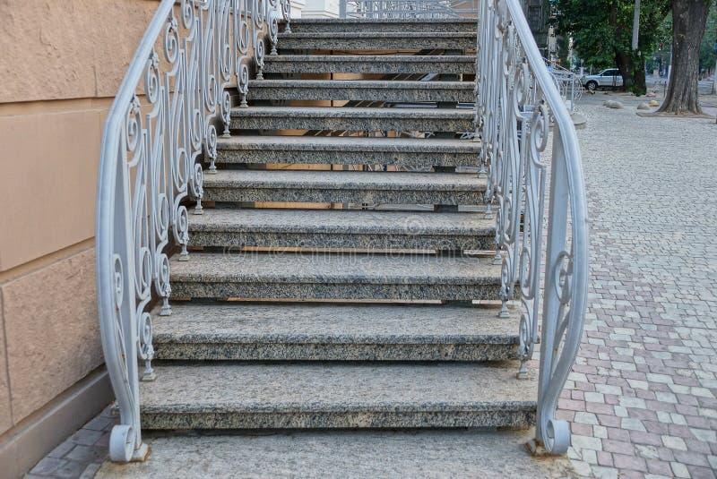 Серые конкретные шаги лестниц с поручнями около стены дома на тротуаре стоковые фото