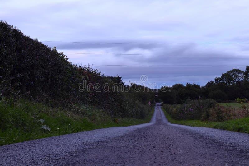Серые облака над дорогой стоковое фото