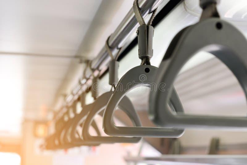 Серые пластиковые ручки на рельсах потолка для пассажира положения, ручки в системе метро или метро или быстрого переезда массы стоковое изображение rf