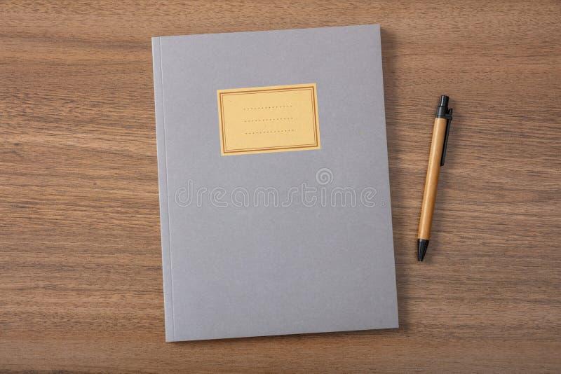 Серые тетрадь или дневник школы, старомодные, на деревянном столе, пустой ярлык, космос для текста, взгляд сверху стоковые изображения rf