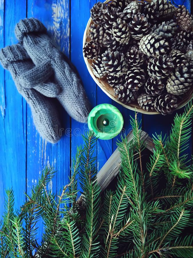 Серые mittens, оформление конусов сосны, зеленая свеча и ветви ели на постаретых выдержанных деревянных досках стоковая фотография