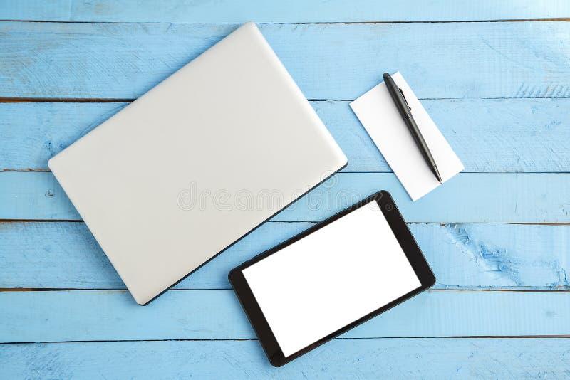 Серый ноутбук, черный планшет, небольшая бумажная тетрадь и черная ручка на голубой деревянной предпосылке r стоковая фотография rf