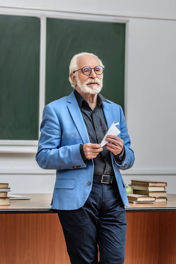 серый профессор волос держа самолет бумаги стоковое фото