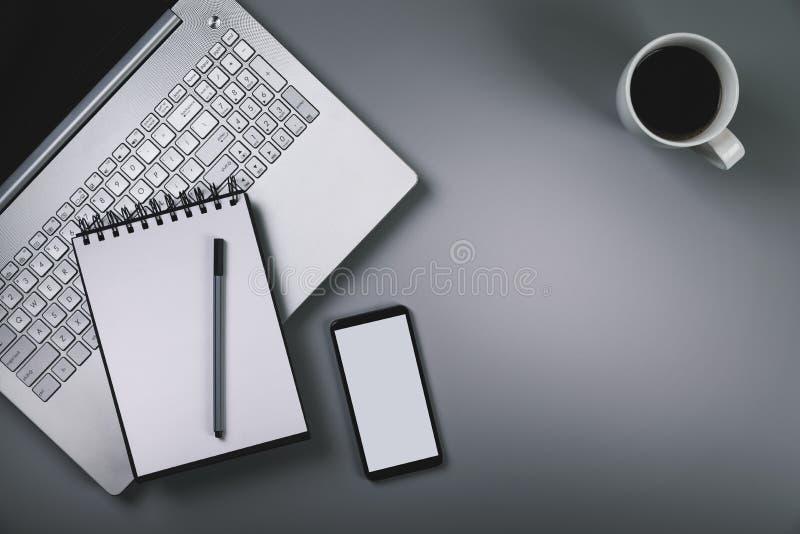 Серый стол с чашкой кофе smartphone компьтер-книжки Взгляд сверху с co стоковое изображение
